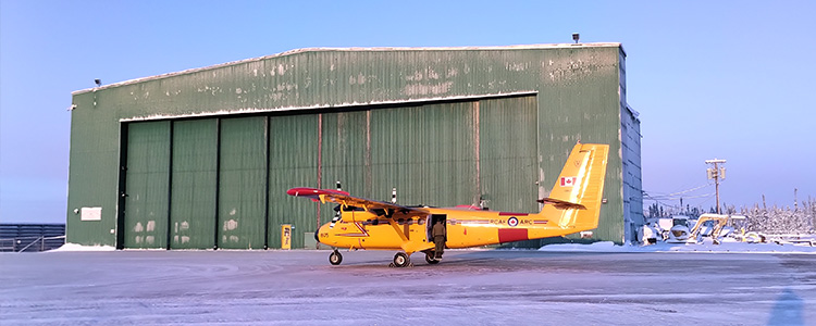 A Twin Otter aircraft parks outside of the ILS hangar on a cold morning at the Inuvik Airport.