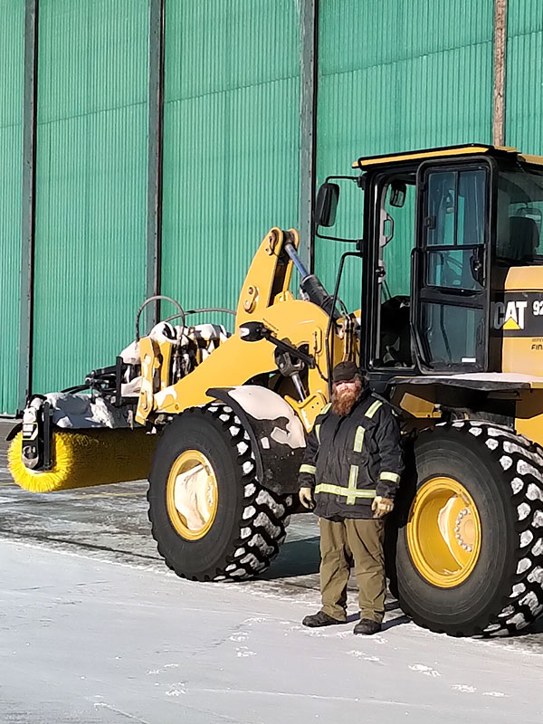 Alex Klapatiuk pictured with heavy equipment in front of the ILS hangar in Inuvik.