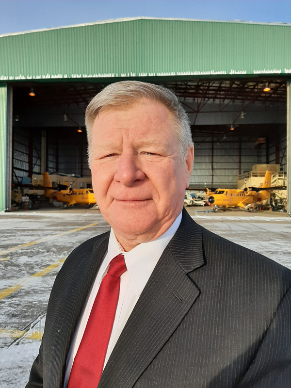 President Les Klapatiuk pictured in front of the ILS hangar.